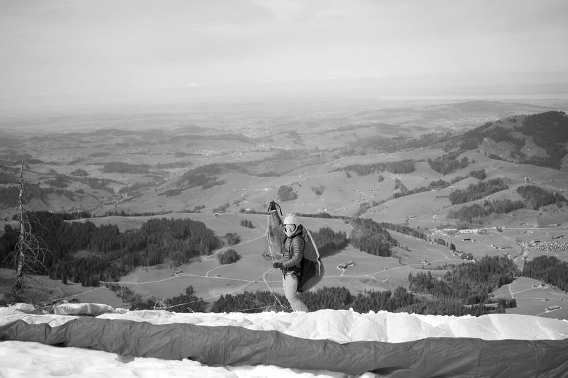 Man with parachute on mountain against sky