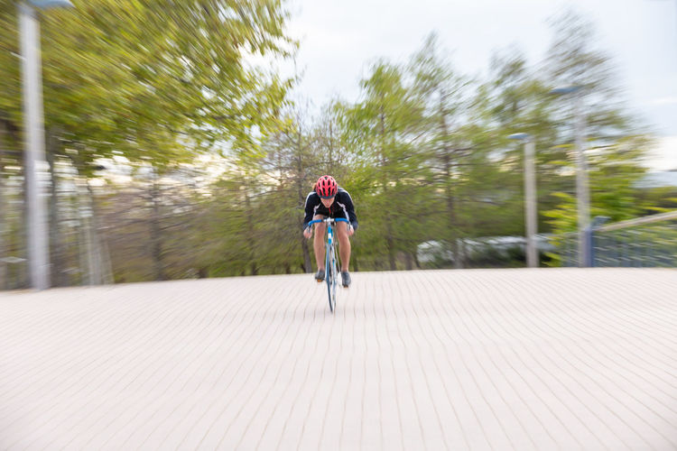 Rear view of woman riding bicycle on footpath