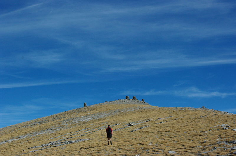 Rear view of man walking on mountain against blue sky