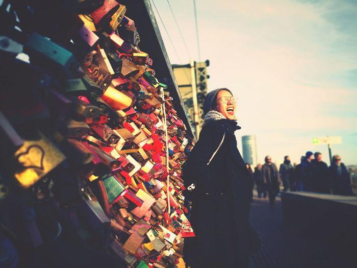 Woman standing by love locks on bridge