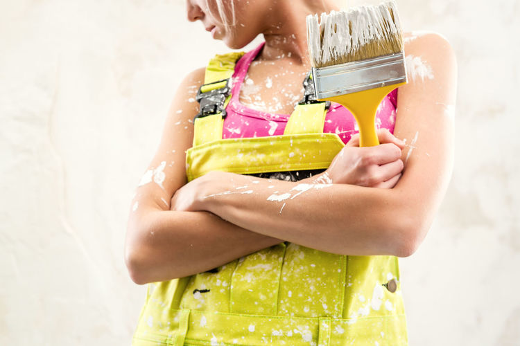 Midsection of woman in coverall holding paintbrush while standing against wall
