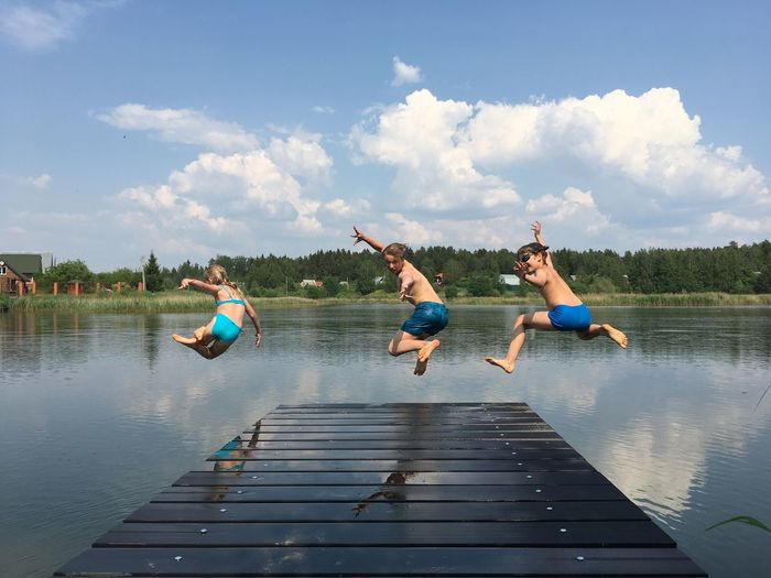 People jumping on lake against sky