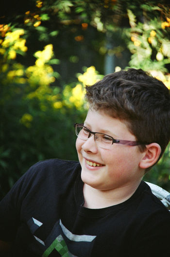 Close-Up Of Happy Teenage Boy Looking Away While Sitting On Chair Against Plants