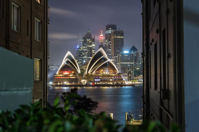 Illuminated Sydney Opera House By Bay In City At Night