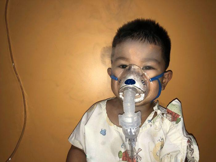 Portrait Of Boy Inhaling Vapor Against Wall