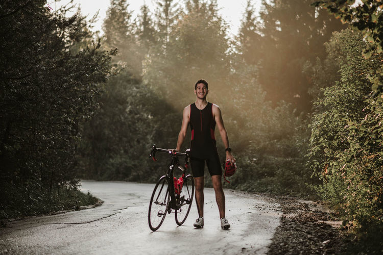 Full length of young man with bicycle walking on road against plants