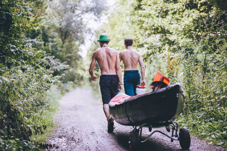 Rear view of shirtless friends carrying boat in forest