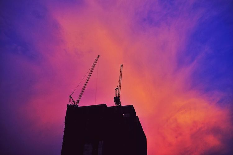 Low angle view of silhouette crane by building against sky during sunset