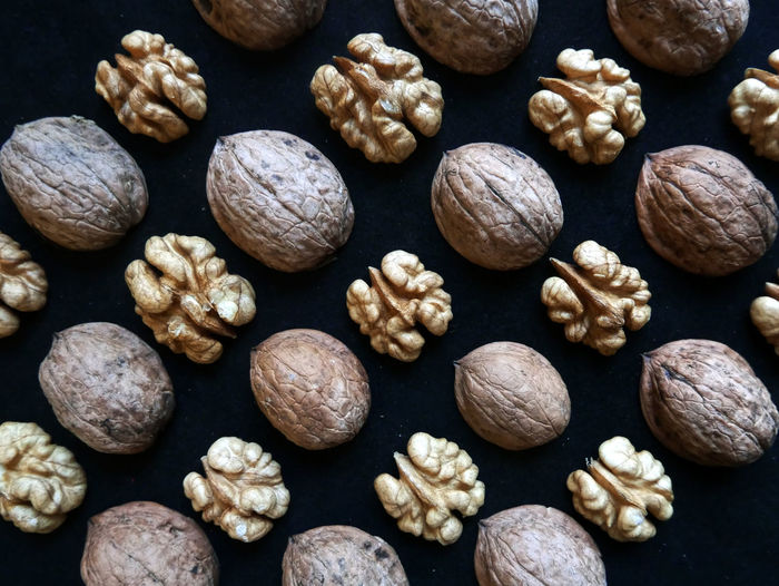 Full frame shot of walnuts over black background