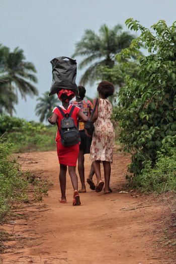 Rear View Of Friends Walking On Dirt Road