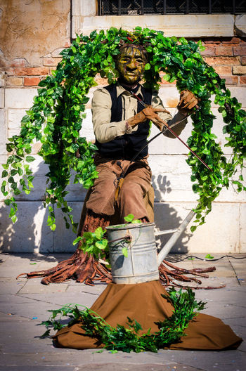 musician disguised as tree entertains tourists in Venice Venice Carnival; Costume; Day Mask; Men; Musical Instrument String; Musical Instrument; One Person; Outdoors Statue Street String Instrument; Venice Carnival; Violin;