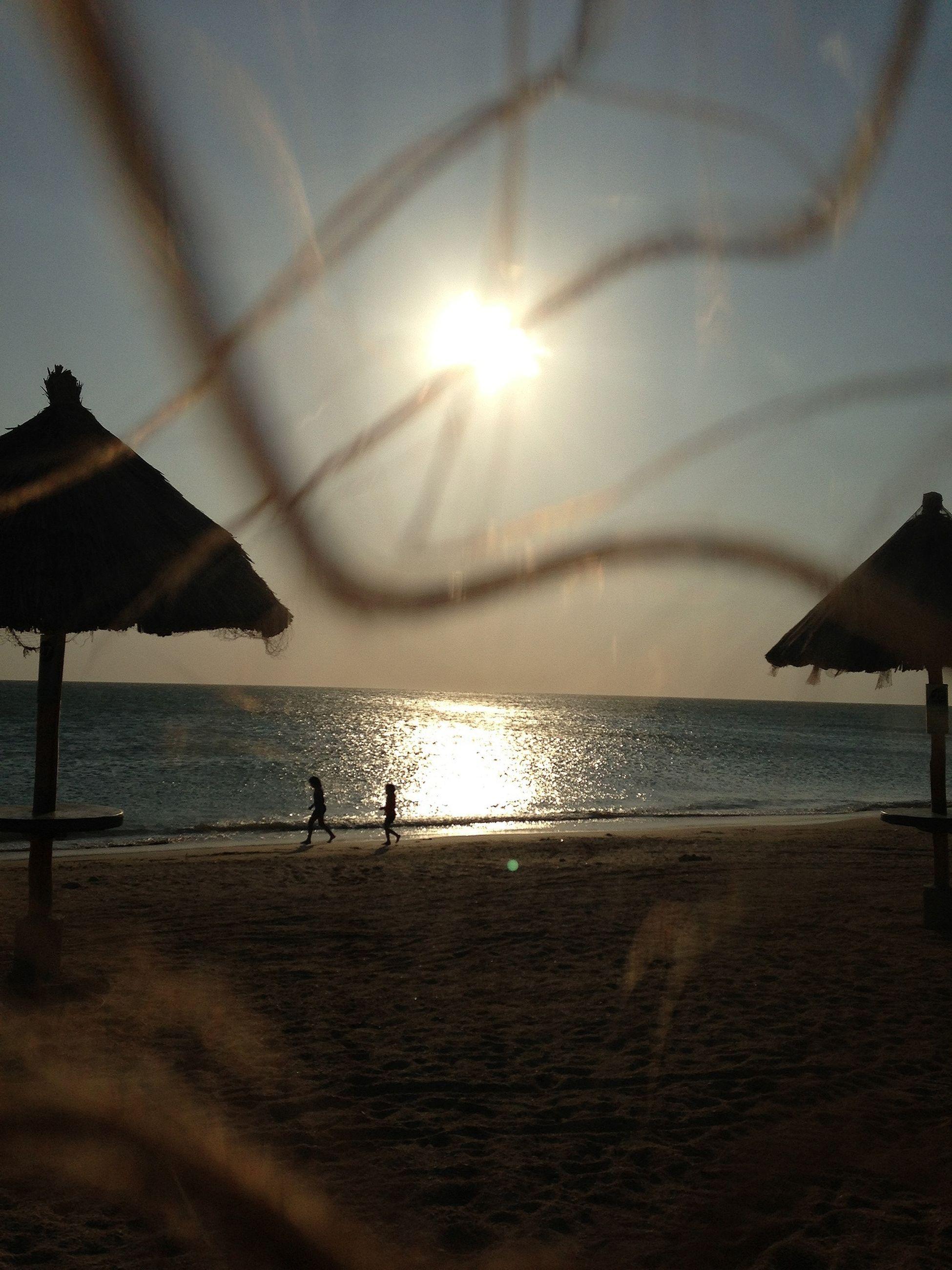 sea, horizon over water, beach, water, sun, shore, tranquil scene, scenics, tranquility, sky, sand, beauty in nature, sunlight, sunset, nature, idyllic, silhouette, sunbeam, reflection, vacations