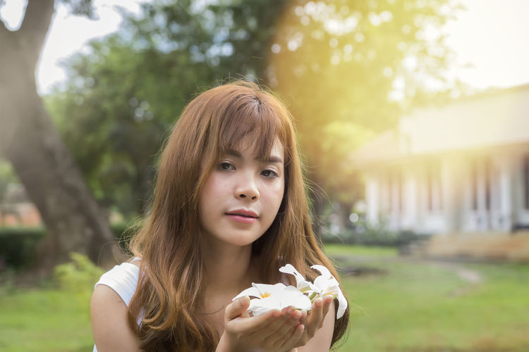 Close-up portrait of young woman holding white flowers in yard