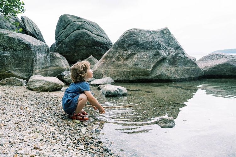 Rear view of boy on rock by lake