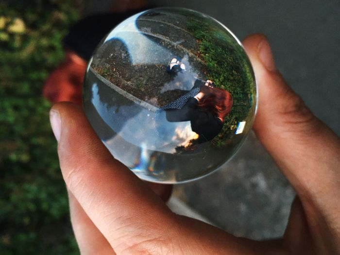 Cropped hand holding crystal ball with reflection