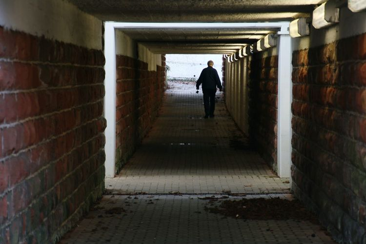 Rear View Of Man Walking In Corridor