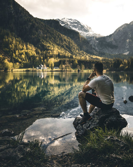 Rear view of man sitting on rock by lake