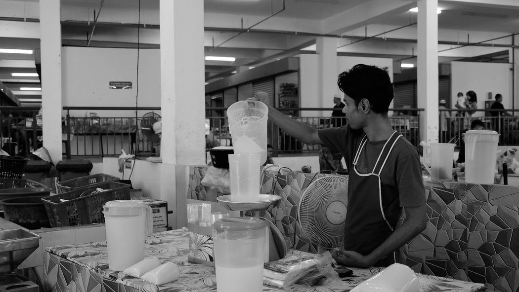 young man filling up coconut milk in plastic Coconut Milk Freshness Market Adult Adults Only Day Indoors  Market Stall Measure Men Occupation One Person People Real People Sell Selling Standing Wet Market Working Workshop Young Adult