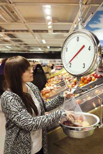 Midsection of woman standing by food in store