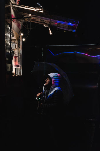 Side view of man using smart phone at night