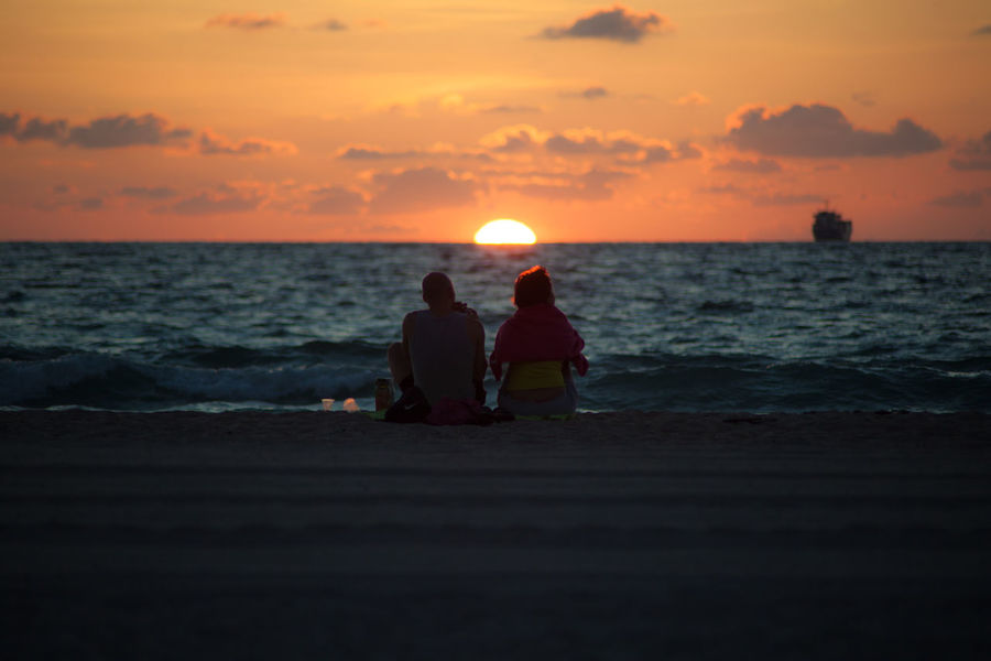 Silhouette of couple against sunrise over Atlantic Ocean in Miami Beach, Florida Anonymous Atlantic Ocean Beach Beauty In Nature Couple Early Horizon Over Water Horizontal Love Morning Nature Orange Outdoors Romance Sea Silhouette Sitting Sky Sun Sunrise Unrecognizable People Water