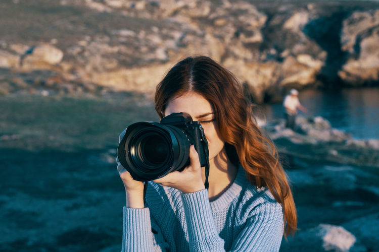 Portrait of woman photographing camera
