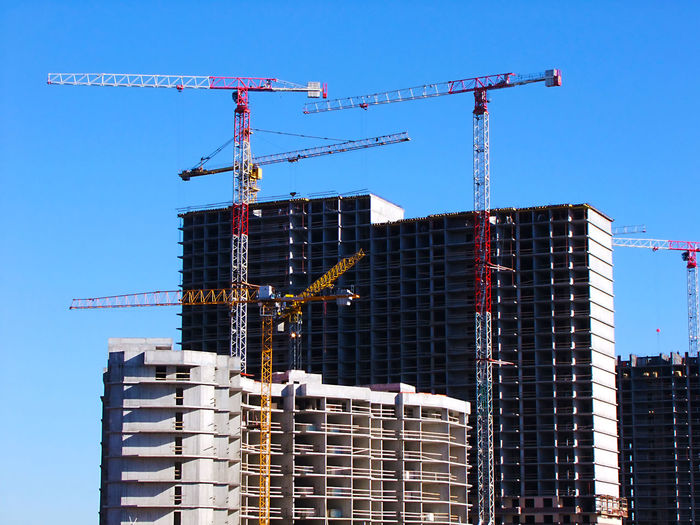 Low Angle View Of Cranes And Incomplete Buildings Against Clear Sky