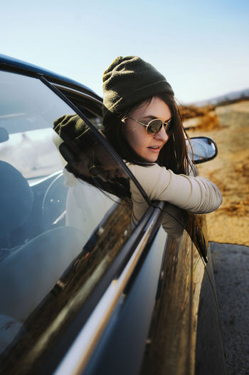 Side view of woman peeking through car window