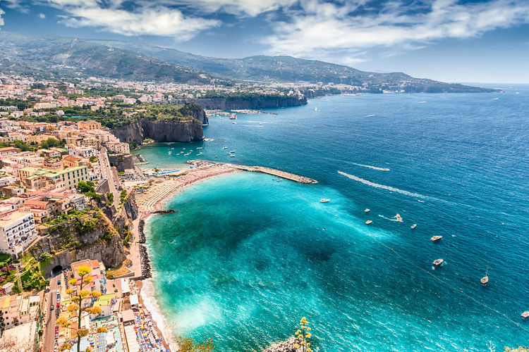 Scenic aerial view of Sorrento, Neapolitan Riviera, Italy, during summertime Aerial View Architecture Beach Beauty In Nature Blue City Cloud - Sky Day High Angle View Mountain Nature Nautical Vessel No People Outdoors Scenics Sea Sky Tranquility Travel Destinations Tree Water