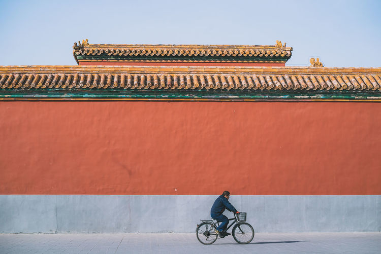 Man riding bicycle on building against sky