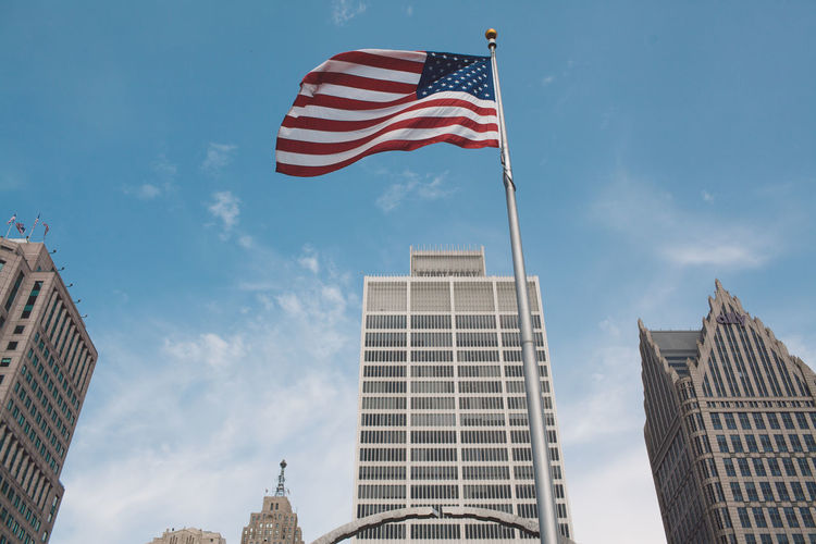 Low Angle View Of Flag Against Buildings And Sky
