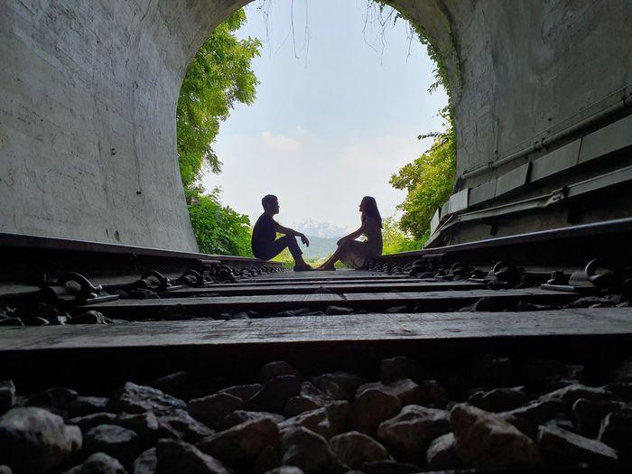 People sitting on railroad track against sky
