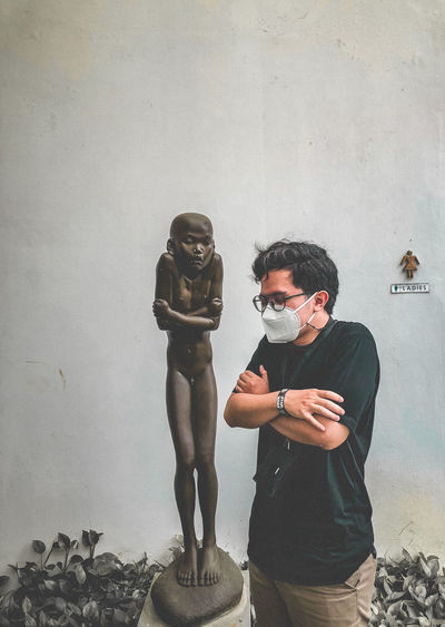 Man and statue against wall
