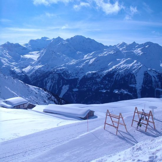 Scenic view of snow covered field and mountains against sky