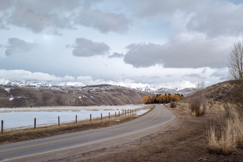 Curved road heading to the Teton mountains Yellow Lines Curved Road Cloud - Sky Road Snow Sky The Way Forward Winter Direction No People Empty Road
