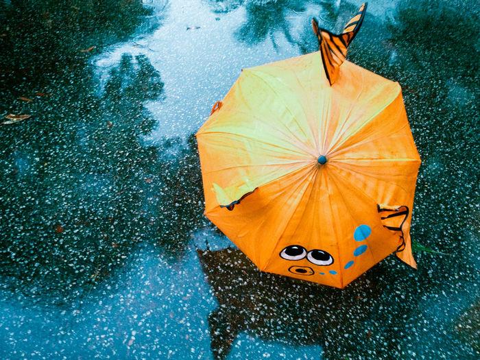 High angle view of orange umbrella on wet footpath during rain
