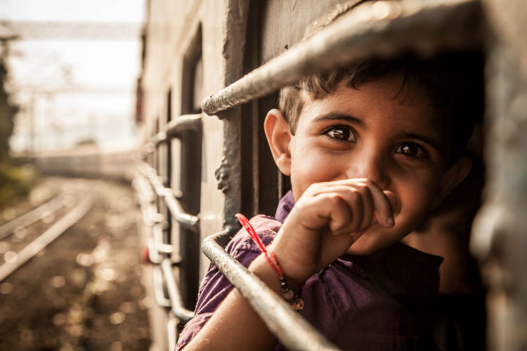 Portrait of boy looking through train window