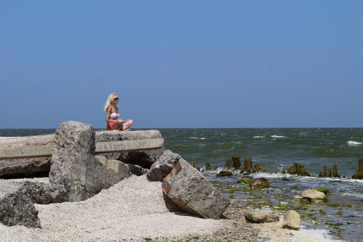 Woman Sitting On Rock Formation At Beach Against Clear Sky