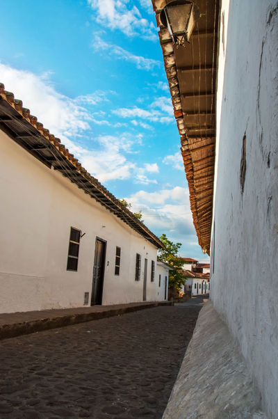 Looking down an old cobblestone street. America Architecture Blue Bucaramanga Building Cobblestone Colonial Day Exterior Girón Historic History Latin Old Outdoors Santander Sky South Spanish Street Tourism Town Travel Urban Wall