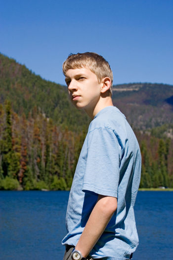 teenager with hand in trouser pocket - looking cool Adolescence  Attitude Blond Hair Bored Boy Boys Canada Casual Clothing Cool Cool Attitude Forest Lake Low Angle View Nature One Boy Only One Teenage Boy Only Outdoors Portrait Real People Serious Side View Teenage Boys Teenager Waist Up Water