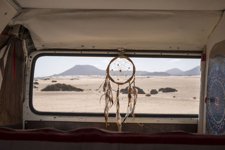 tiny house on wheels with dream catcher near the back window Adventure Arid Climate Beach Beauty In Nature Day Desert Dream Catcher Landscape Mode Of Transport Mountain Mountain Range Nature No People Outdoors Sand Sand Dune Scenics Sea Sky Transportation Travel Vacations Van Life Vehicle Interior Window