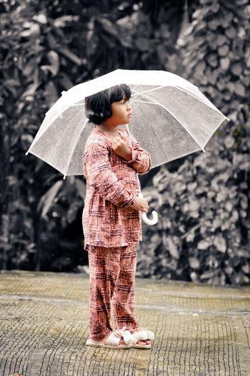 Boy holding umbrella standing during rainy season