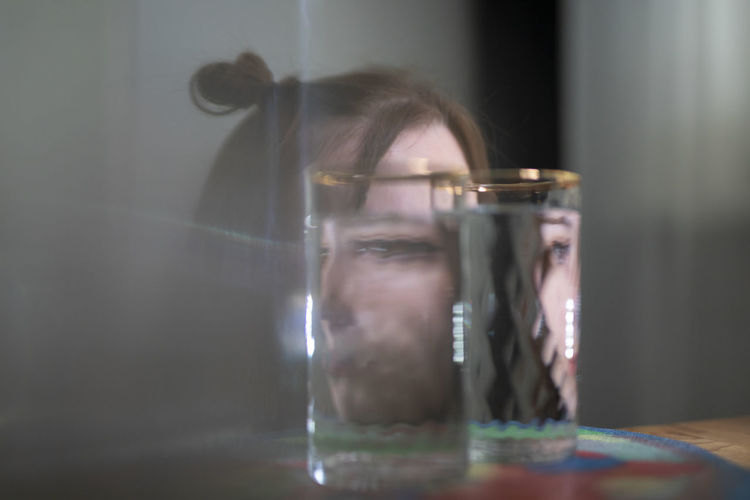 Close-up portrait of woman with glass on table
