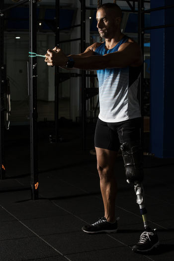 Determined Disabled Man Exercising At Gym