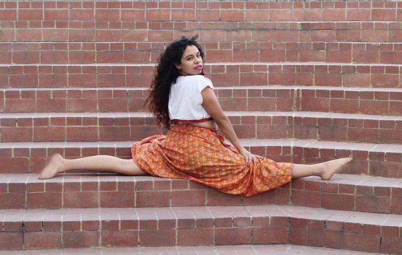 Portrait of woman doing splits on steps