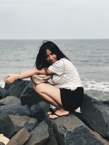 EyeEm Selects Sea Full Length One Person Real People Rock - Object Leisure Activity Young Adult Young Women Water Lifestyles Horizon Over Water Outdoors Casual Clothing Day Nature Sitting Clear Sky Beauty In Nature Beach Scenics Fashion Stories