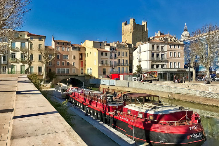 The Canal de la Robine flows underneath the Pont des Marchands at Narbonne in France. Architecture Blue Sky Building Exterior Buildings Built Structure Canal De La Robine Castle Cathedral City Clear Sky Day France Narbonne Nautical Vessel No People Outdoors Pont Des Marchands Travel Destinations Water