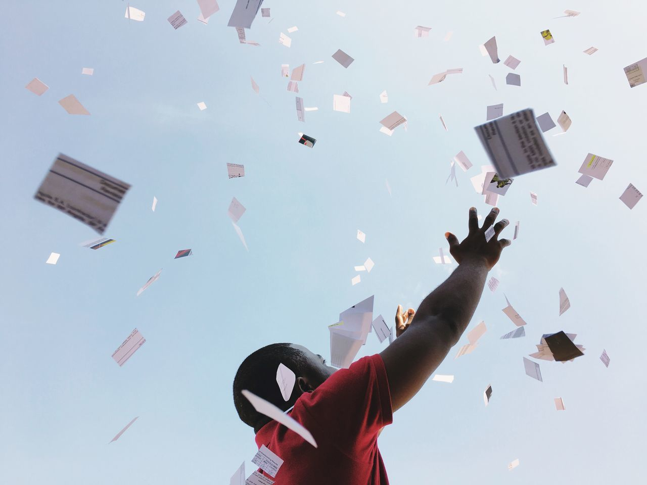 Low angle view of man with papers falling against sky