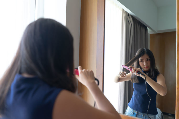 Young Asian woman straightening hair with hair straightener while looking into the mirror at home. Beautiful girl lifestyle, beauty concept. Fashion Straightener Woman Activity Adult Beautiful Woman Girl Hair Hairstyle Headshot Holding Indoors  Leisure Activity Lifestyles Long Hair Mirror One Person Portrait Preparation  Real People Reflection Standing Women Young Adult Young Women