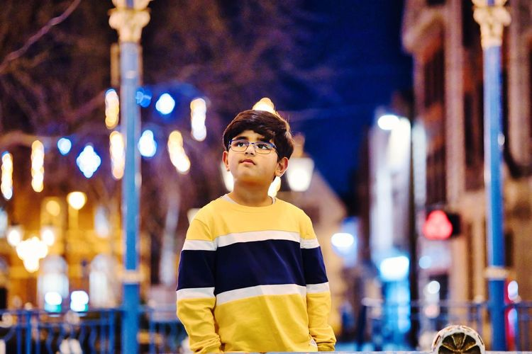 Portrait of boy standing against illuminated lights at night